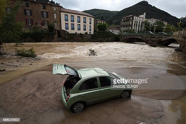 This photo taken on September 13 2015 in Lodeve in the Herault department of France shows a car displaced by floodwaters of La Lergue the river that...