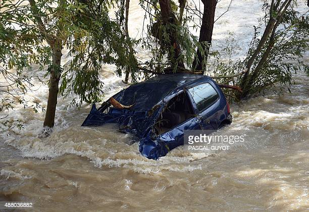 This photo taken on September 13 2015 in Lodeve in the Herault department of France shows a automobile taken away by floodwaters of La Lergue the...