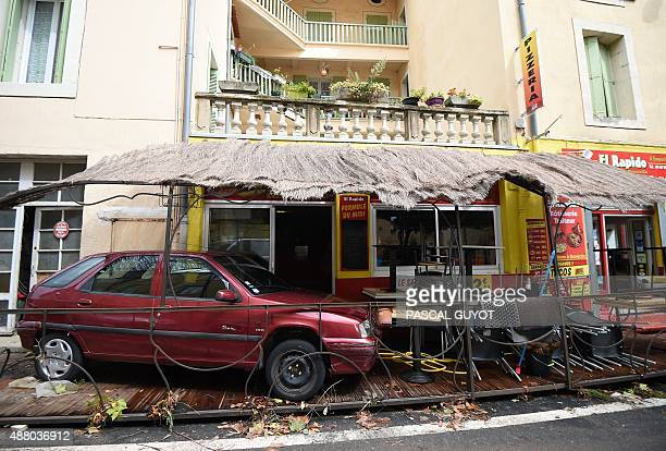 This photo taken on September 13 2015 in Lodeve in the Herault department of France shows an automobile on a cafe's terrace after being taken away by...