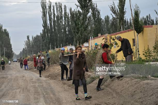 This photo taken on September 13 2019 shows people on a street in a small village where ethnic Uighurs live on the outskirts of Shayar in the region...