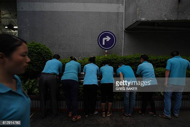 This photo taken on September 14 2016 shows workers washing their hands after dinner outside the canteen at the Huajian shoe factory where about...