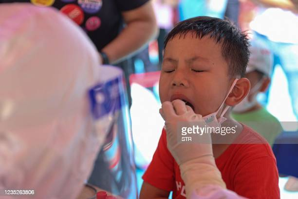 This photo taken on September 14, 2021 shows a child undergoing a nucleic acid test for the Covid-19 coronavirus in Xiamen, in China's eastern Fujian...