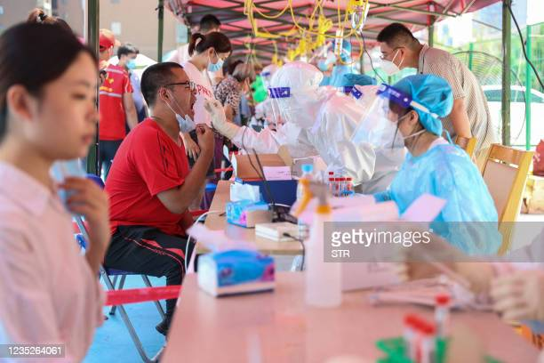 This photo taken on September 14, 2021 shows a resident undergoing a nucleic acid test for the Covid-19 coronavirus in Xiamen, in China's eastern...