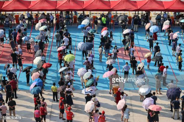 This photo taken on September 14, 2021 shows residents queueing to undergo nucleic acid tests for the Covid-19 coronavirus in Xiamen, in China's...