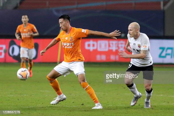 This photo taken on September 15, 2020 shows Shanghai SIPG's Aaron Mooy fighting for the ball during their Chinese Super League football match with...