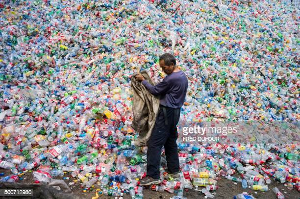 TOPSHOT This photo taken on September 17 2015 shows a Chinese labourer sorting out plastic bottles for recycling in Dong Xiao Kou village on the...