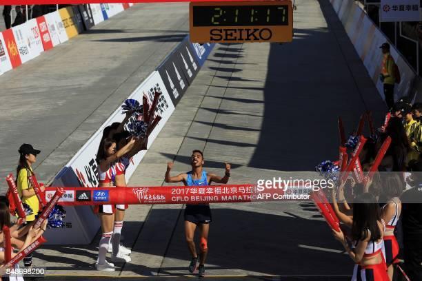 This photo taken on September 17 2017 shows Salah Eddine Bounasr of Morocco celebrating as he wins the 2017 Beijing Marathon in Beijing / AFP PHOTO /...