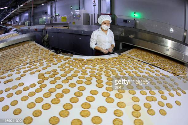 This photo taken on September 17, 2019 shows a worker monitoring a biscuit production line in Huaibei in China's eastern Anhui province. / China OUT