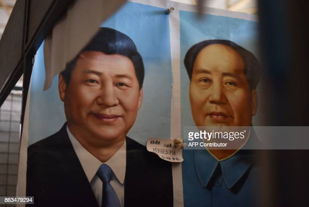 This photo taken on September 19, 2017 shows painted portraits of Chinese President Xi Jinping and late communist leader Mao Zedong at a market in...
