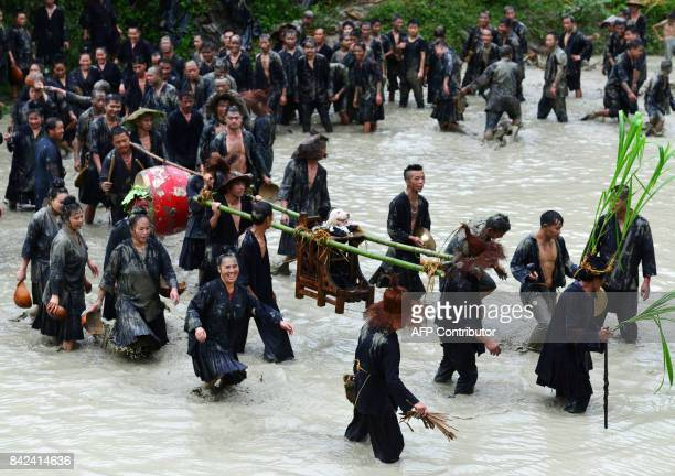 This photo taken on September 2 2017 shows people of Miao ethnic minority carrying a dog in a sedan chair during dog carrying day a traditional local...