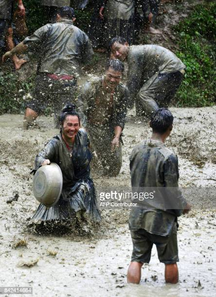 This photo taken on September 2 2017 shows people of Miao ethnic minority splashing mud water to each other during dog carrying day a traditional...