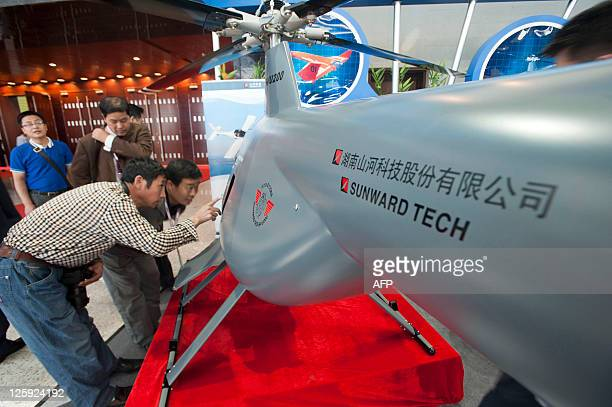 This photo taken on September 21 2011 shows Chinese visitors examining an unmanned helicopter drone from a Chinese manufacturer at the China Aviation...