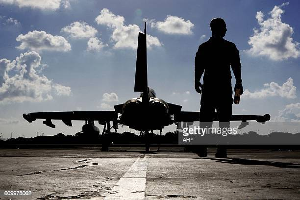 This photo taken on September 22 2016 shows a British soldier walking by a Eurofighter Typhoon fighter jet at Royal Air Force's Akrotiri base in...