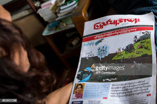 This photo taken on September 22 2017 shows a man looking at a newspaper's front page with a sketch called 'crocodile tears' by one of Myanmar's most...
