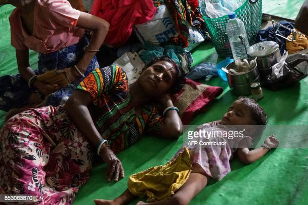 This photo taken on September 22 2017 shows a woman sleeping next to a baby on the floor of a makeshift IDP camp for Hindus at a disused football...