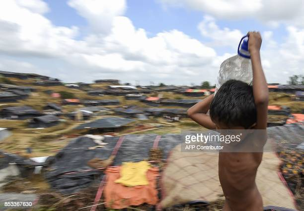 This photo taken on September 22 2017 shows a young Rohingya refugee carrying water at the Balukhali refugee camp in Ukhia The World Health...