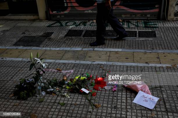 This photo taken on September 24 2018 shows flowers in front of a jewelry shop were a man was beaten to death in the center of Athens Athens...