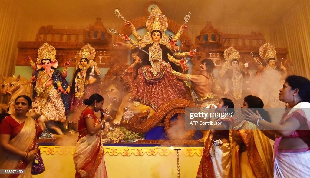 This photo taken on September 25 2017 shows Indian women offering prayers to the Hindu deity Durga at the opening ceremony of the Durga Puja festival...
