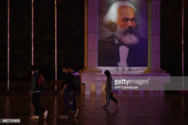 This photo taken on September 26 2017 people walking past a portrait of revotionary socialist Karl Marx in the main East is Red Square in Nanjie...