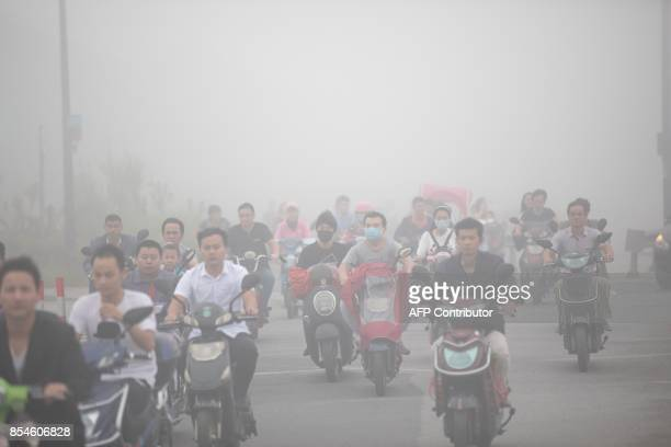 TOPSHOT This photo taken on September 26 2017 shows people driving in a heavy fog caused by hot and humid weather in Hangzhou in China's eastern...