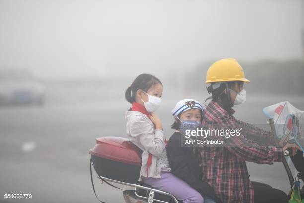 This photo taken on September 26, 2017 shows people wearing face masks in a heavy fog caused by hot and humid weather in Hangzhou, in China's eastern...