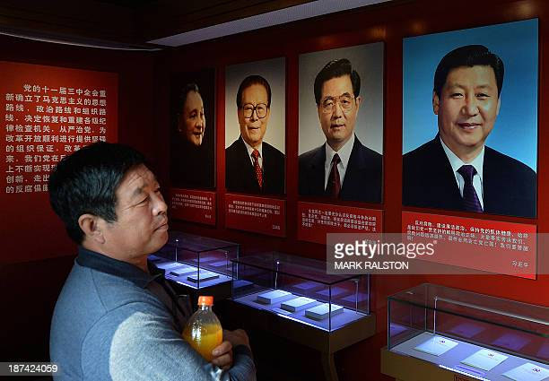 This photo taken on September 28 2013 shows portraits of the Chinese President Xi Jinping along with his predecessors Hu Jintao Jiang Zemin and Deng...