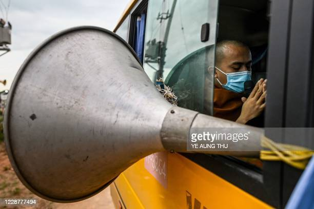 This photo taken on September 28, 2020 shows a Buddhist monk chanting protective verses against the spread of the COVID-19 novel coronavirus from a...