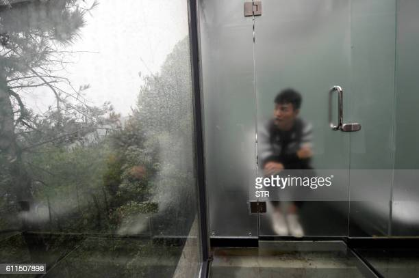 This photo taken on September 29 2016 shows a tourist visiting a glasswalled public toilet in Shiyan Lake scenic area in Changsha central China's...