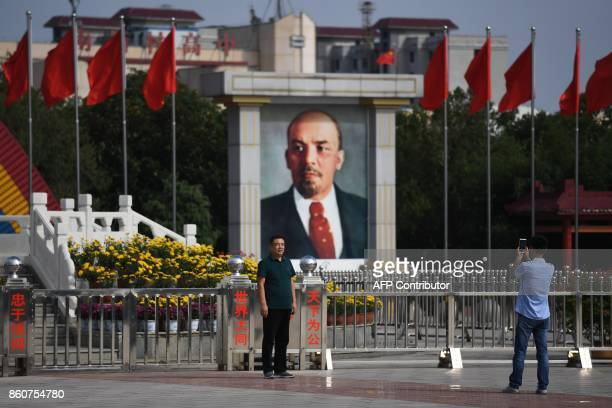 This photo taken on September 29 2017 shows a man posing for photos near a portrait of communist revolutionary and Soviet leader Vladimir Lenin in...