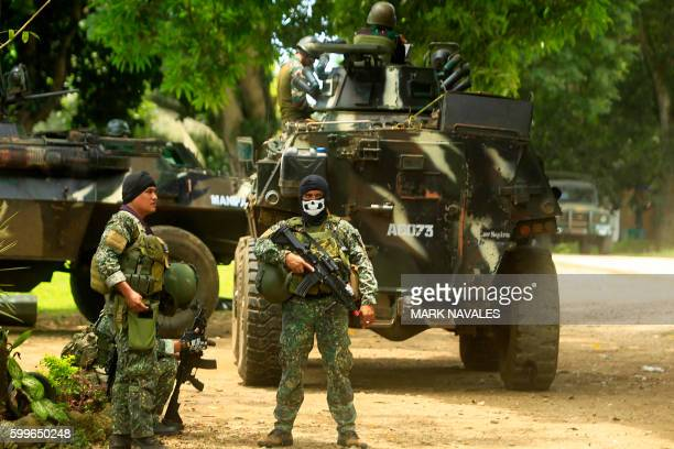 This photo taken on September 5 Philippine soldiers standing guard next to an Armored Personnel Carrier inside a military camp in Jolo Sulu province...