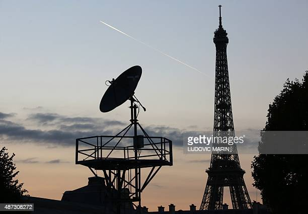 This photo taken on September 8 2015 shows a plane flying past the Eiffel Tower at sunset AFP PHOTO / LUDOVIC MARIN