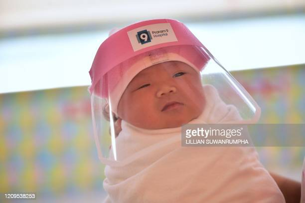 TOPSHOT This photo taken through a glass window at a maternity ward shows a newborn baby wearing a face shield in an effort to halt the spread of the...