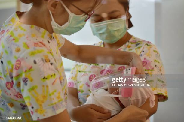 This photo taken through a glass window at a maternity ward shows nurses putting a face shield on a newborn baby, in an effort to halt the spread of...