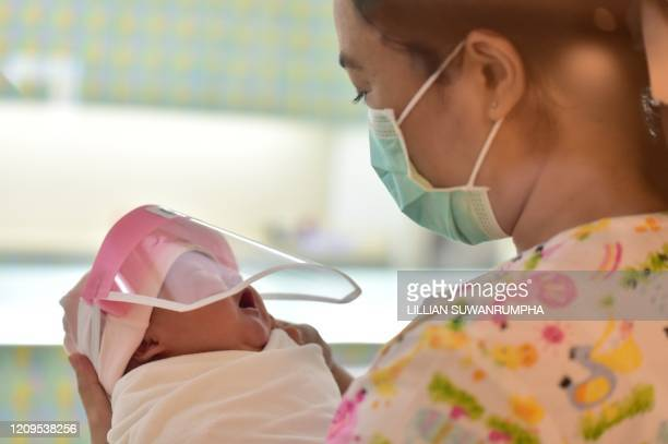 This photo taken through a glass window at a maternity ward shows a nurse holding a newborn baby wearing a face shield, in an effort to halt the...