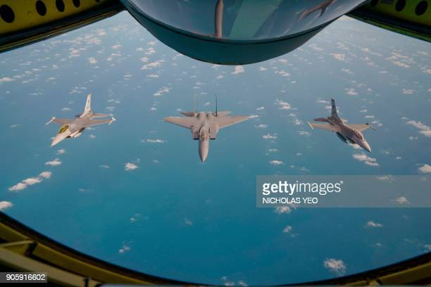This photo taken through the port window of a Republic of Singapore Airforce KC135R Stratotanker shows an RSAF F15SG airsuperiority fighter flanked...