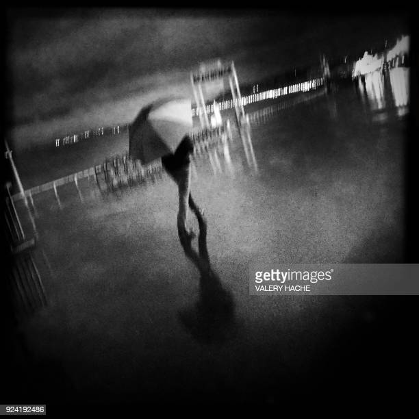 This photo taken with a mobilephone shows a man walking under the rain on the 'Promenade des Anglais' in the French Riviera city of Nice on February...