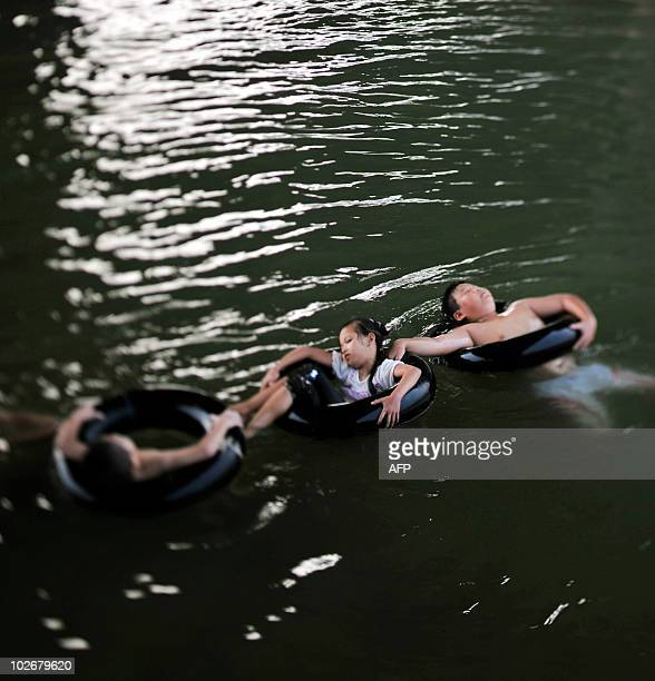 This photo taken with a tilt and shift lens shows Chinese children swiming in the Yangtze river in Wuhan in central China's Hubei province on July 6...