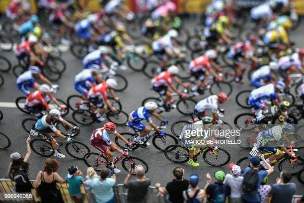 TOPSHOT This photo taken with a tilt and shift lens shows the pack of riders taking the start of the sixth stage of the 105th edition of the Tour de...