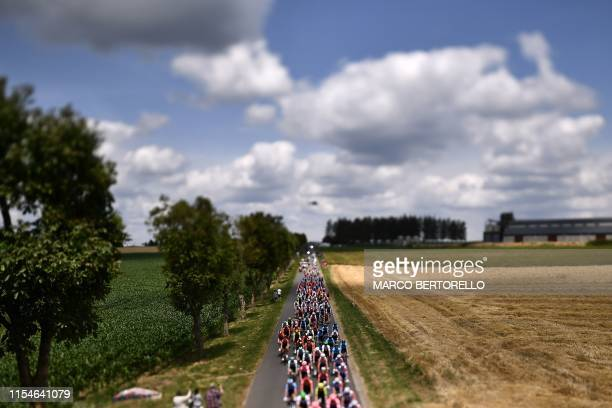 This photo taken with a tilt and shift lens shows the pack riding in the countryside during the third stage of the 106th edition of the Tour de...
