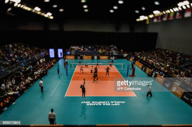 This photo taken with a tiltandshift lens shows shows Thailand's Bamrungsuk Hattaya serving the ball against the Philippines players during their...