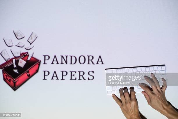 This photograph illustration shows hands typing on a keyboard in front of the logo of Pandora Papers, in Lavau-sur-Loire, western France, on October...