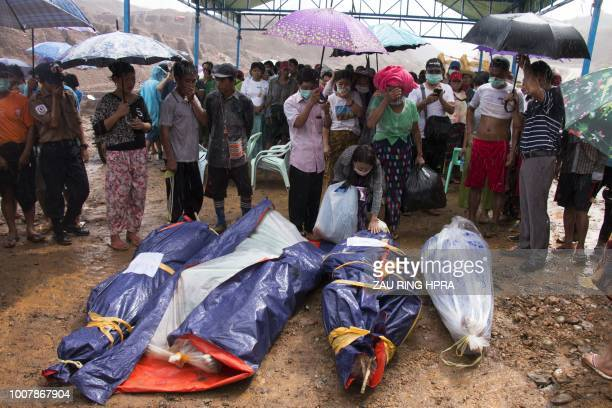 TOPSHOT This photograph is taken on July 25 2018 shows relatives reacting after search and rescue volunteers found the bodies of miners killed in a...