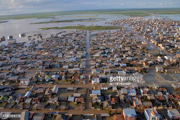 TOPSHOT This photograph released by the Iranian news agency Fars News on March 23 shows flooded streets in the northern Iranian village of Agh Ghaleh...