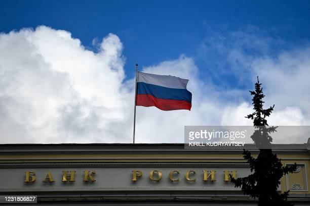 This photograph shows a general view of the Russian Central Bank headquarters as the Russian flag flies, in downtown Moscow, on March 19, 2021. -...