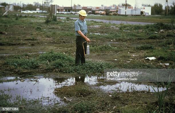 This photograph shows a man using a handcarried compressed air sprayer apply larviciding oil to mosquito breeding pools 1981 Standing pools of...