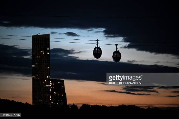This photograph shows cable cars connecting Vorobyovy Hills and the Luzhniki stadium over the Moskva river in Moscow late on July 30, 2021.