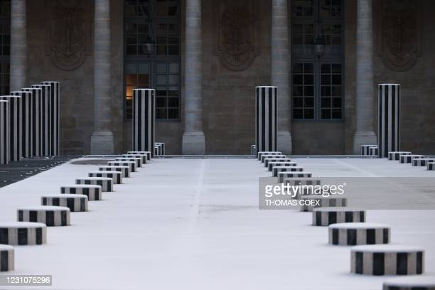 This photograph shows the snow-covered columns of The Colonnes de Buren , an art installation by French artist Daniel Buren in the inner yard of the...
