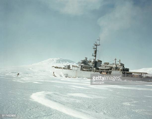 This photograph shows the USS Glacier, , as it pounds the ice of the MC Murdo Sound in the shadow of Mt. Erebus, the only known active volcano on the...