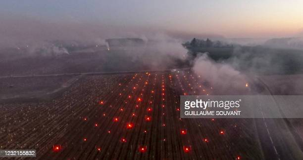 This photograph taken at dawn on April 7, 2021 shows an aerial view of smoke rising from fires lit in the vineyards to protect them from frost at the...