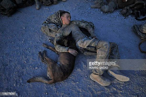 This photograph taken August 15 2011 shows US Army Specialist Justin Coletti of US Forces Afghanistan K9 combat tracker team resting with Dasty a...